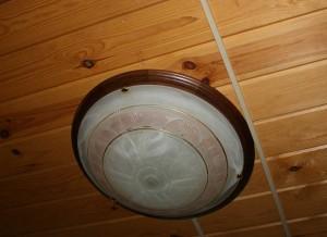 Круглый светильник с коричневым кантом на обшитом деревом потолке.