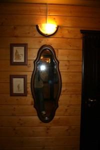 на фоне дерева, зеркало, картинки и светильник.